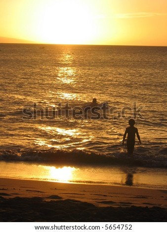 Boys playing in the ocean at sunset