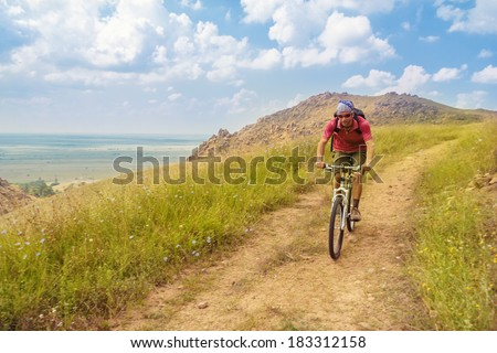 Boys rides a bike in Macin mountains, Tulcea, Romania. - stock photo