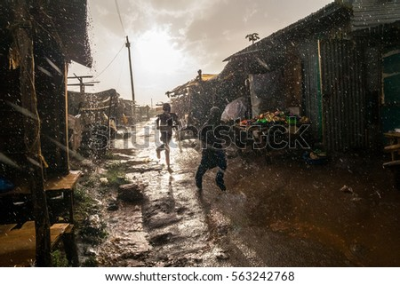 Boys running through african market during rain