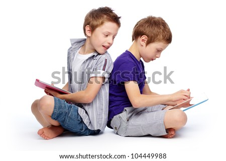 Boys sitting back to back using hi-tech digital pads - stock photo