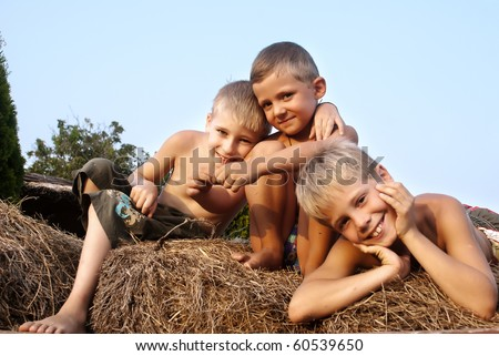 boys sitting on a hay bale on sky background - stock photo