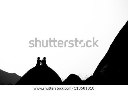 Boys talk on Rocks in Joshua Tree National Park - stock photo