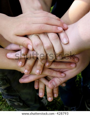 Boys' team with hands stacked together - stock photo