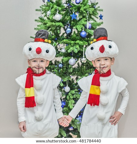 Boys, twins in carnival costumes of snowmen. Stand hold hands before the Christmas fir-tree.