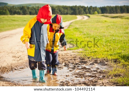 Boys walking in a mud puddle - stock photo