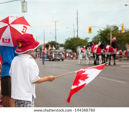 Boys watching a Canada Day parade. Aurora, Ontario, Canada. - stock photo