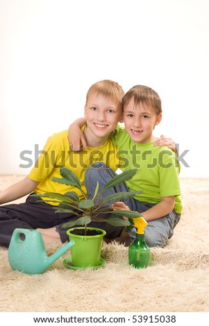 boys watering flower