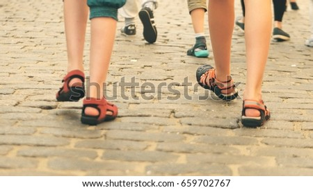 Boys wearing shorts and sandals walk on cobblestone pavement