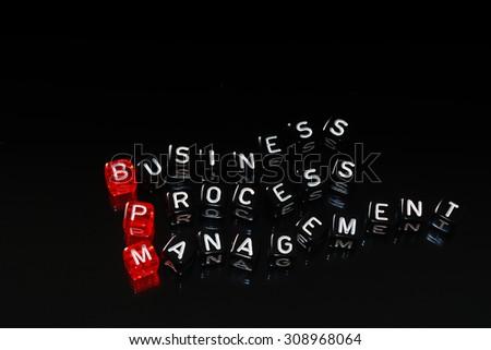 BPM Business Process Management written on cubes on black - stock photo
