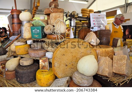 BRA, ITALY - SEPTEMBER 22, 2013: Different types of mature hard cheese on the stand. Hard cheese produced by stirring and draining a mixture of curd and whey in Bra, Italy on September 22, 2013. - stock photo