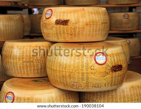 BRA, ITALY - SEPTEMBER 22, 2013: Wheels of Parmesan - famous italian hard cheese made from raw cow's milk, often grated over dishes and named after producing areas near Parma, Italy. - stock photo