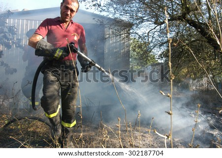 Bracciano, Italy - July 14, 2005: Severe Fires destroy forest in Italy. Italian firefighters work surrounded by the smoke to extinguish the fire, July 14, 2005 in Bracciano, Lazio, Italy.