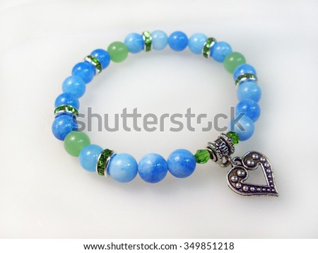 Bracelet stone and glass beads with pendants - stock photo
