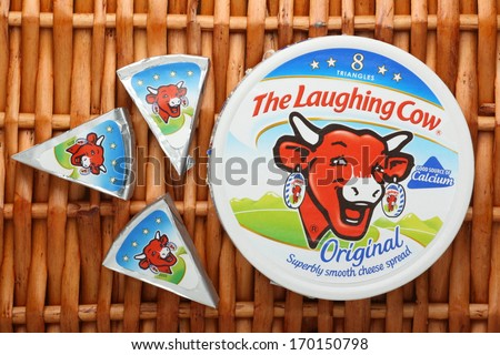 Bracknell, England - January 07, 2014: A box of The Laughing Cow Cheese Spread and three portions of foil wrapped cheese on a wicker background. The company was founded in France in 1921.
