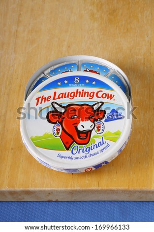 BRACKNELL, ENGLAND - JANUARY 06, 2014: An opened box of The Laughing Cow cheese spread on a chopping board. The company was founded in France in 1921.
