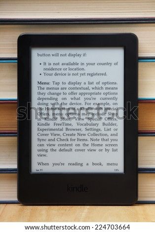 Bracknell, England - October 20th, 2014: A Kindle Touch Reader standing in front of old hardback books. Manufactured by Amazon the device is a portable library of books and other publications - stock photo