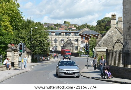 BRADFORD ON AVON - AUG 17: Street view of people and cars in the old town on Aug 17, 2014 in Bradford on Avon, UK. The historic Wiltshire town was a wool industry centre during industralisation. - stock photo