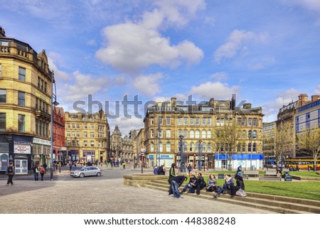 Bradford, West Yorkshire, England : 1 April 2011 - A group of young people sitting on the steps in front of Bradford Town Hall, surrounded by the city's sandstone architecture.