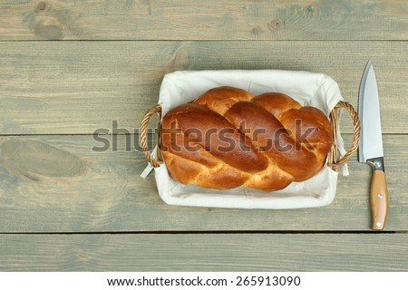 braid bread in a basket on wooden background - stock photo