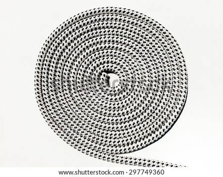 Braided polyester black and white marine rope coiled in a circle on deck of boat - stock photo