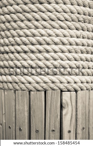 Braided white rope wrapped around a wooden post.  Wooden slats with metal screws are visible below the rope.  can be used as background or texture and has copy space - stock photo