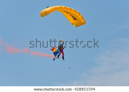 "BRAILA, ROMANIA - MAY 28, 2016: Recreational flying airplane with smoke on air show demonstration flight. ""Bors de Peste 2016 - Fly In"" AIR SHOW. Parachute jumper with smoke"