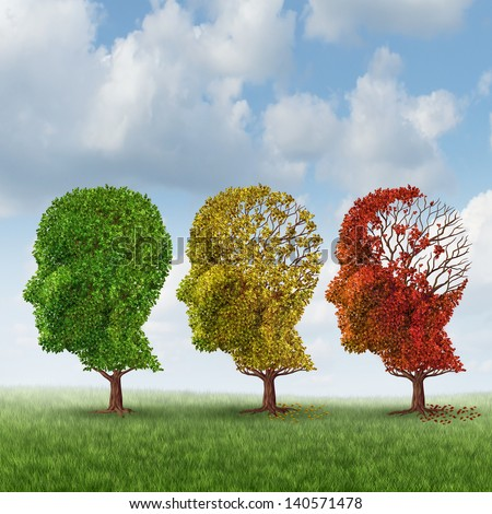 Brain aging and memory loss due to Dementia and Alzheimer's disease as a medical icon of a group of color changing autumn fall trees shaped as a human head losing leaves as intelligence function. - stock photo