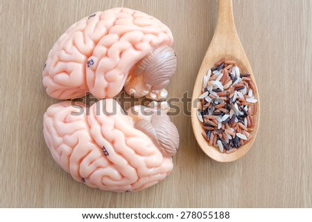 brain and mix of rice on wooden background with healthy concept