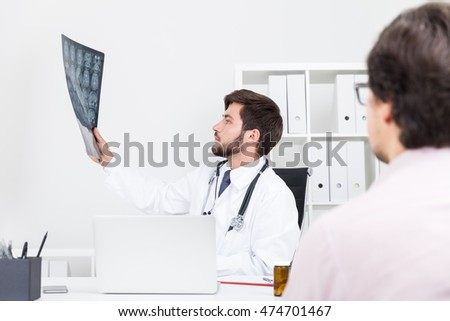 Brain surgeon is looking at x ray image of his patient and trying to give him the right diagnosis. Concept of scrupulous doc