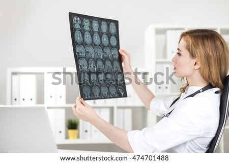 Brain surgeon is looking at x ray images of her patient sitting at her workplace. Concept of difficult decision making