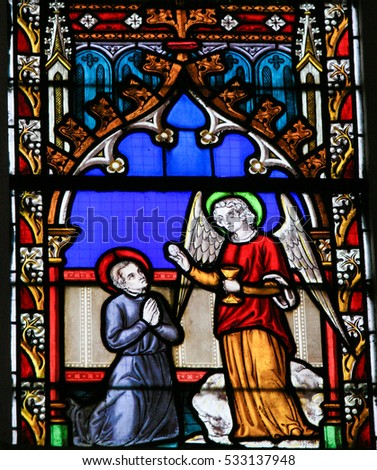 BRAINE-LE-CHATEAU, BELGIUM - JULY 31, 2009: Stained Glass window in the Church of Braine-le-Chateau, Wallonia, Belgium, depicting an Angel giving sacramental bread to a Catholic Saint