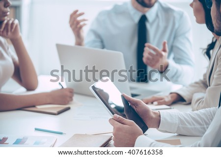 Brainstorm. Close-up part of group of people discussing something while sitting at the office table - stock photo