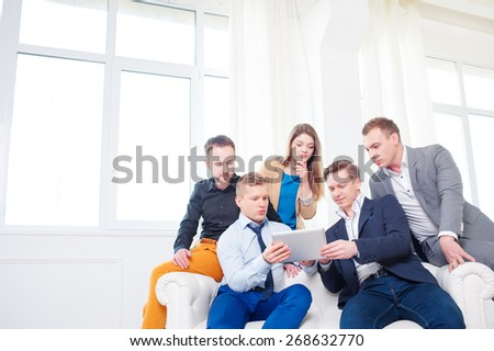Brainstorm. Group of colleagues wearing casual looking at the tablet computer together and discussing the project while sitting on the white sofa against windows in office. - stock photo