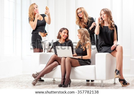 Brainstorm. Group of young cheerful gorgeous caucasian businesswomen in black dresses looking at the laptop together and laughing while sitting on the white sofa with little dog near it. - stock photo