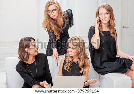Brainstorm. Group of young cheerful gorgeous caucasian businesswomen in black dresses looking at the laptop together and talking while sitting on the white sofa. - stock photo