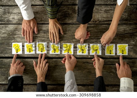 Brainstorming and teamwork concept with a group of diverse business people each holding out a card with a shining light bulb arranged in a row conceptual of ideas, inspiration and innovation. - stock photo