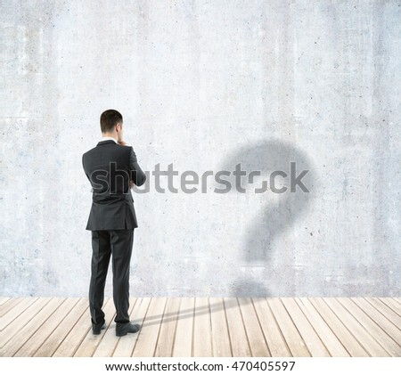 Brainstorming businessman with question mark shadow in room with concrete wall and wooden floor