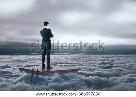 Brainstorming concept with thinking businessman standing on brick pedestal in dull cloudy sky - stock photo