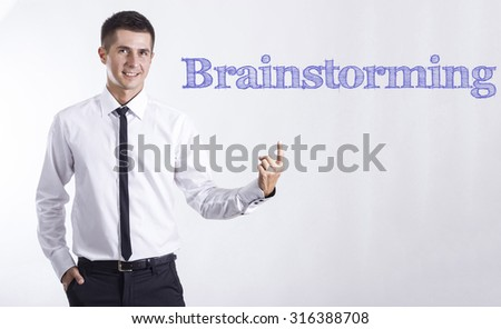 Brainstorming - Young smiling businessman pointing on text