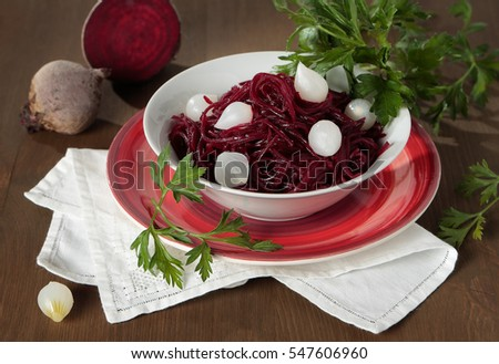 Braised beets with small pickled onions and parsley in a bowl