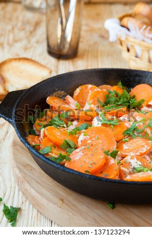 Braised carrots with cream in a pan, food
