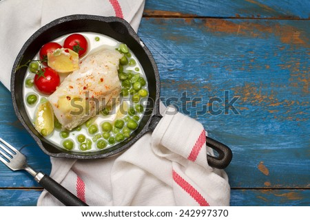 Braised codfish with green peas, cherry tomatoes, cream and ginger - stock photo
