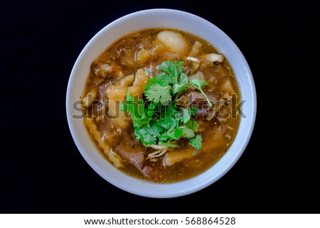 Braised Fish Maw in Red Gravy put the bowl in white against a black background. Sprinkle with parsley on top.
