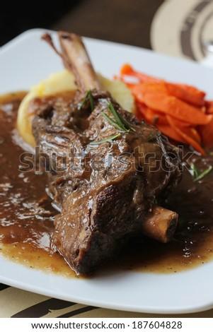 Braised lamb shank in mint and rosemary gravy - stock photo