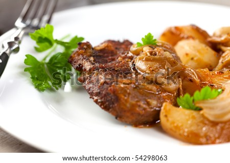 Braised pork chop with potatoes and onion in sauce