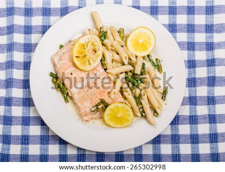 Braised salmon with asparagus and penne pasta with sliced lemons - stock photo