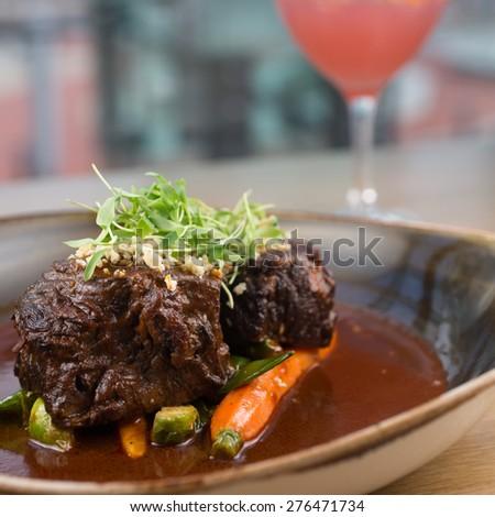 Braised short ribs with ancho cacao rub, seasonal vegetables and horseradish gremolata  - stock photo