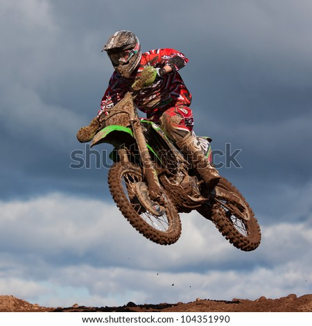 BRAMPTON, ENGLAND - MARCH 18: An unidentified motocross rider takes part in the East Cumbria Motocross, Championship Round 1 at Low Gelt Motocross track in Cumbria, England on March 18, 2012. - stock photo