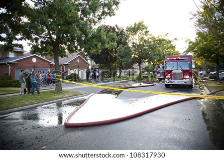 BRAMPTON, ONTARIO -  JULY 20 2012 - Crowd gathers to watch a house fire burning at 20 Esker Drive in Brampton Ontario on July 20, 2012 - stock photo