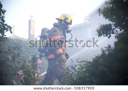 BRAMPTON, ONTARIO -  JULY 20 2012 - Firefighter walks through the backyard as fellow firefighters try to douse a house fire burning at 20 Esker Drive in Brampton Ontario on July 20, 2012